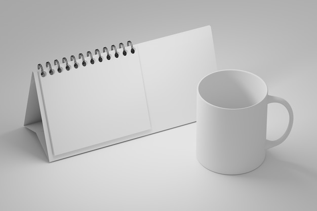 Office table template with white standing spiral calendar and blank coffee mug cup on white Premium Photo