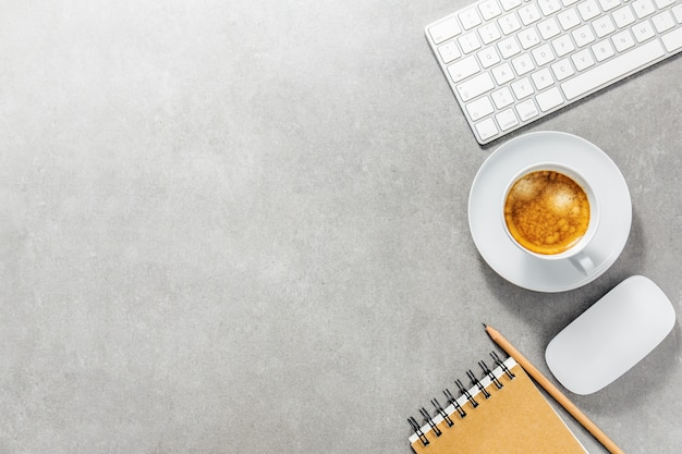 Office table with cup of coffee, keyboard and notepad Premium Photo