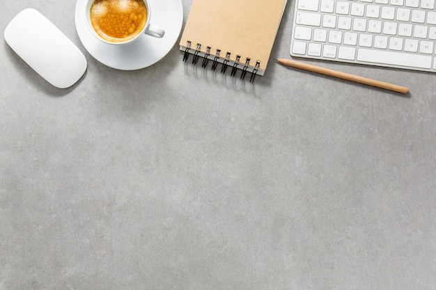 Office table with cup of coffee, keyboard and notepad Free Photo