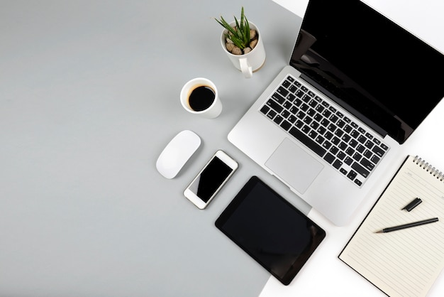 Office table with  laptop computer, notebook, digital tablet and smartphone on two tone ba Premium P