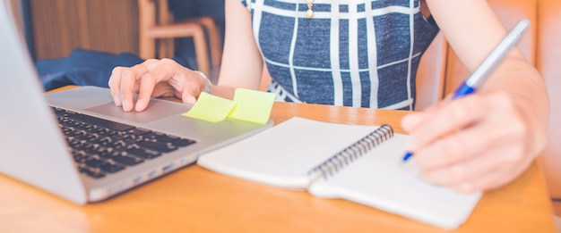 女性の手がコンピューターで作業し、officeのペンでメモ帳に書いています。webバナー。 Premium写真