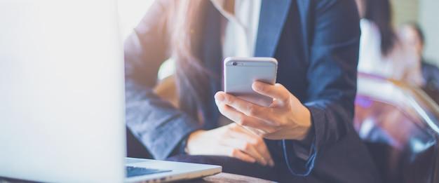 ビジネスの女性の手は、office.webバナーで携帯電話を使用しています。 Premium写真