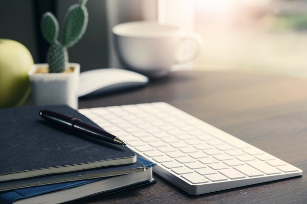Office workspace with computer keyboard and supplies on over light wooden table. Premium Photo