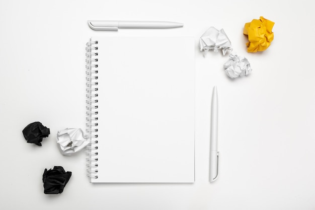 Office workspace with an empty notebook and crumpled paper Premium Photo