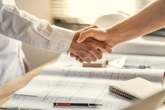 Officer teamwork is happy and shake hands to celebrate in success of finish in job planning about home building construction project Premium Photo