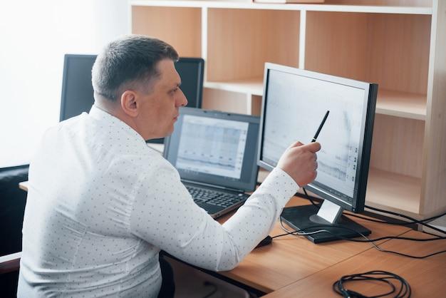 In camicia bianca ufficiale. l'esaminatore del poligrafo lavora in ufficio con l'attrezzatura della sua macchina della verità Foto Gratuite