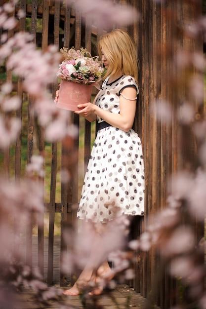 フェンスの近くにフラワーボックスを保持している水玉ドレスのサイドビューogブロンドの女性 Premium写真