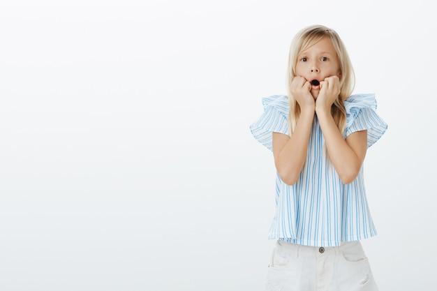 ああ、神よ、ママが来て見て。好奇心旺盛なヨーロッパの女の子は金髪で、開いた口の近くで手をつないで集中して見つめ、テレビを見て、灰色の壁にショックを受けました 無料写真