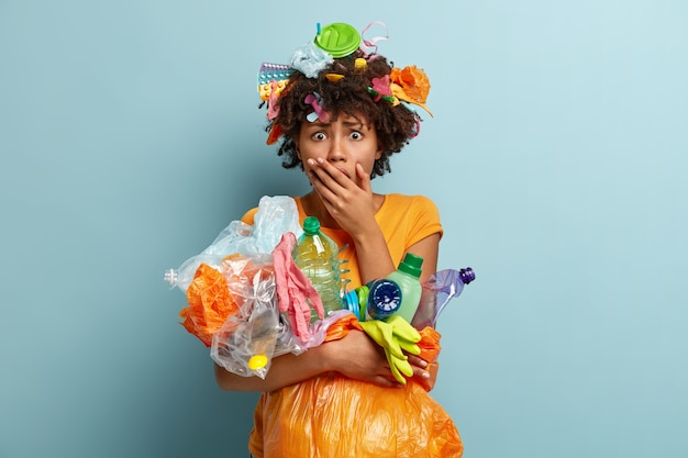 Oh no, usa meno plastica. la femmina timorosa sorpresa emotiva copre la bocca, raccoglie la spazzatura di plastica, fissa con espressione omg, impegnata con la pulizia e il riciclaggio, isolata contro il muro blu Foto Gratuite