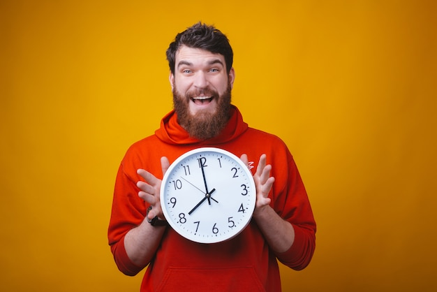Oh no, what time is it. bearded  surprised man is holding a white clock on yellow space. Premium Photo