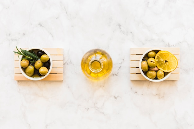 Oil bottle between the two bowls of olive with rosemary and lemon slice Free Photo