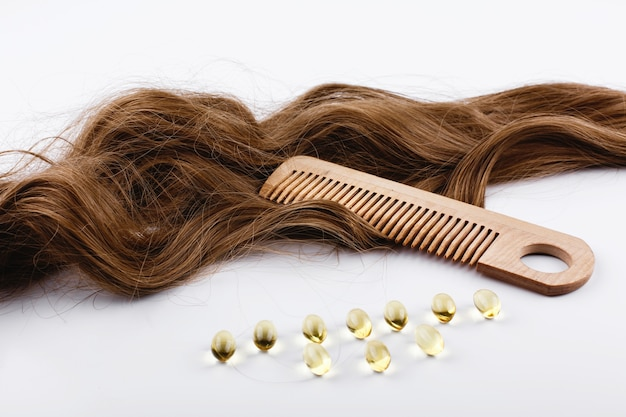 Oil capsules with vitamin e lie on brown hair curls Free Photo