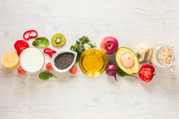 Oil; fruits; vegetables and oats arranged in a row on white textured background Free Photo