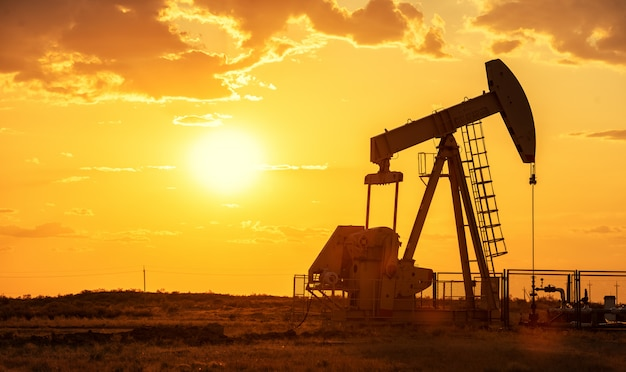 Oil pump oil rig energy industrial machine for petroleum in the sunset Premium Photo
