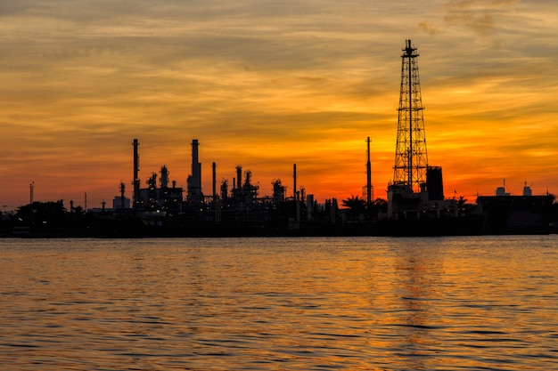 Oil refinery silhouette along the river at sunrise time Premium Photo