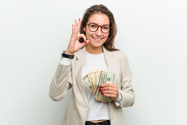 陽気な自信を持ってokジェスチャーを示すドル紙幣を保持している若いヨーロッパビジネス女性。 Premium写真