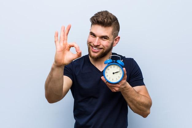 目覚まし時計を明るく、自信を持ってokのジェスチャーを保持している若い白人男。 Premium写真