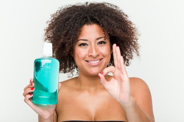 うがい薬元気で自信を持ってokジェスチャーを保持している若いアフリカ系アメリカ人女性。 Premium写真