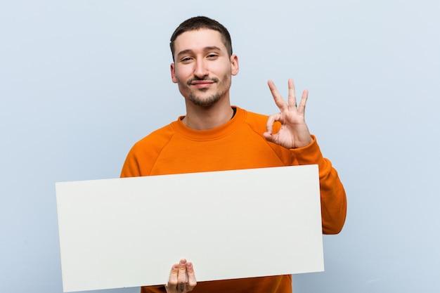 陽気な自信を持ってokジェスチャーを示すプラカードを保持している若い白人男。 Premium写真