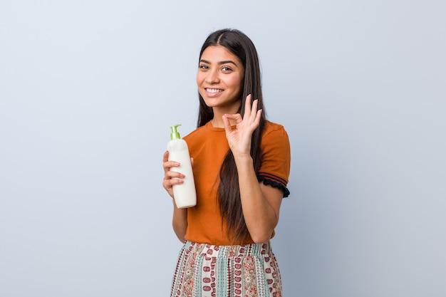 陽気な自信を持ってokのジェスチャーを示すクリームボトルを保持している若いアラブ女性。 Premium写真
