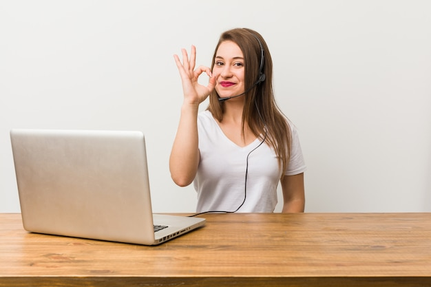 若いテレマーケティング女性陽気なと自信を持ってokのジェスチャーを示します。 Premium写真