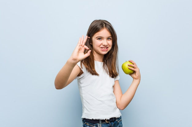 [ok]ジェスチャーを示す陽気で自信を持って緑のリンゴを保持している白人少女。 Premium写真