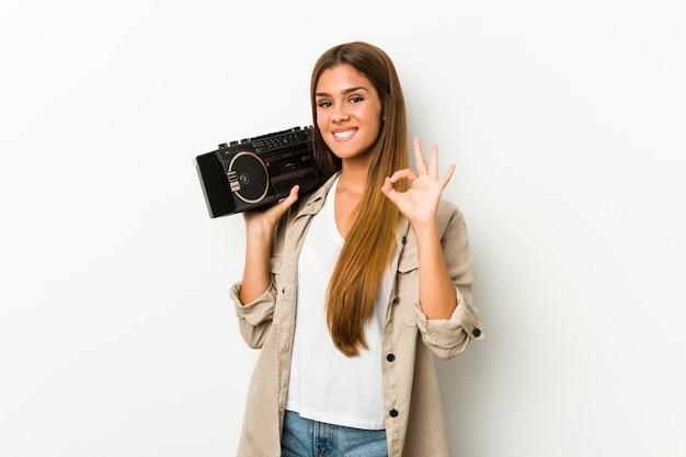 ゲットーブラスターを保持している若い白人女性は明るく、自信を持ってokのジェスチャーを示します。 Premium写真