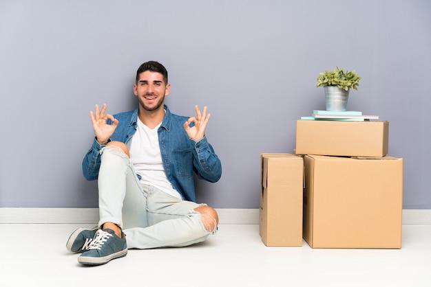 指でokの標識を示すボックスの間で新しい家に移動するハンサムな若い男 Premium写真