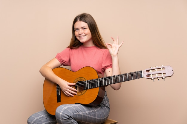 指でokサインを示す分離上のギターとウクライナのティーンエイジャーの女の子 Premium写真