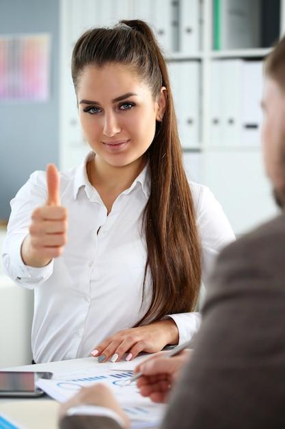 女性の腕はオフィスで会議中にokまたは確認を示します Premium写真