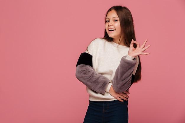 探しているとokのジェスチャーを示すセーターで笑顔の女の子 無料写真
