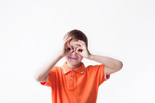 白い背景に[ok]手ジェスチャーを通して見る少年の笑顔 無料写真