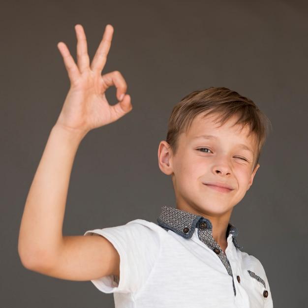 Okのサインを与える小さな男の子 無料写真