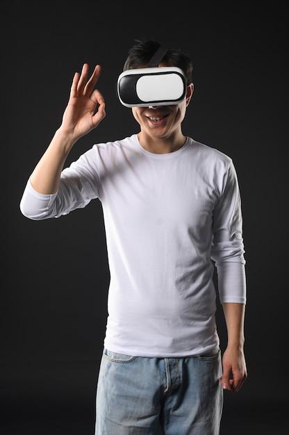 Okの標識を示す仮想現実のヘッドセットを持つ男 無料写真