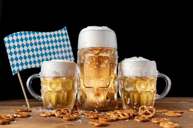 Oktoberfest beer mugs with snacks on a table Free Photo