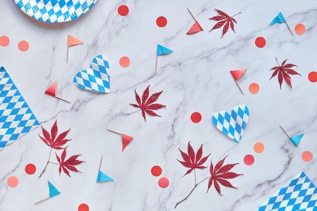 季節の装飾、赤とオレンジ色の紙吹雪とカエデの葉とオクトーバーフェストパーティーの背景。 Premium写真