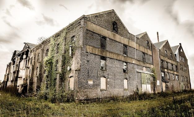 어두운 흐린 하늘 아래 깨진 창문이있는 오래된 버려진 석조 건물 무료 사진