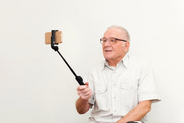 Old active man taking selfie with mobile phone isolated on grey background vlogger blogger concept Premium Photo