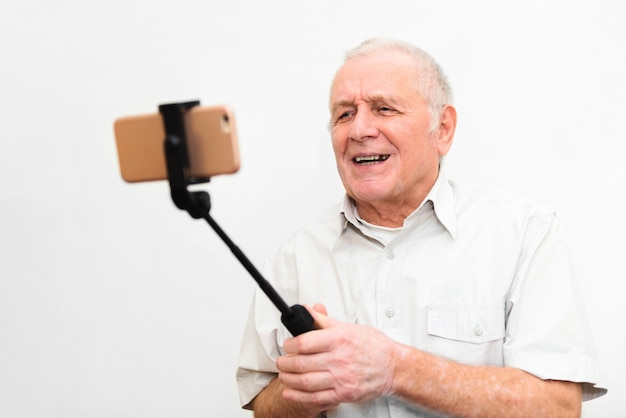 Old active man taking selfie with mobile phone isolated on grey background Premium Photo