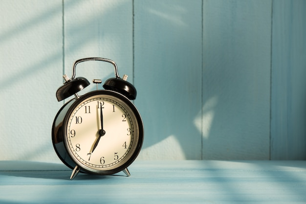Old alarm clock on wooden desk Premium Photo