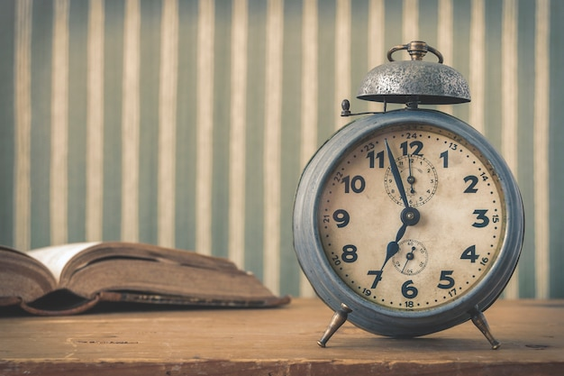 An old alarm clock and an open book Premium Photo