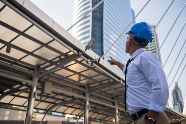 灰色の髪とヘルメットを持つ古いアメリカのエンジニアリングコンサルタントは、近代的な都市の建設現場の建物に指を向けます。 Premium写真