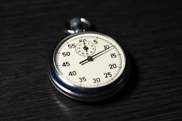 Old analog stopwatch lies on on a dark wooden surface, close-up Premium Photo