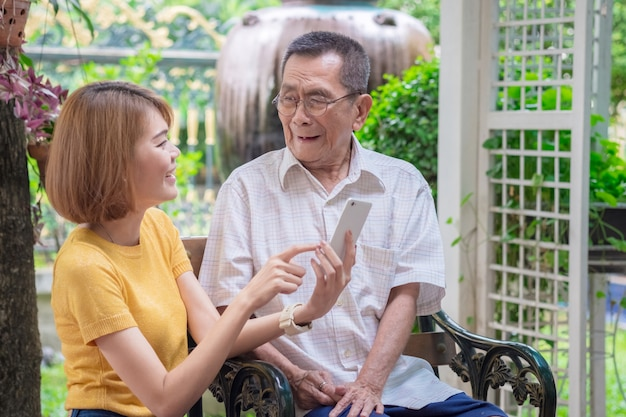 Old asian father and daughter. daughter teaches an elderly father to use a mobile phone Premium Photo