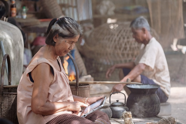 Old asian women are playing tablets in rural thailand. Premium Photo