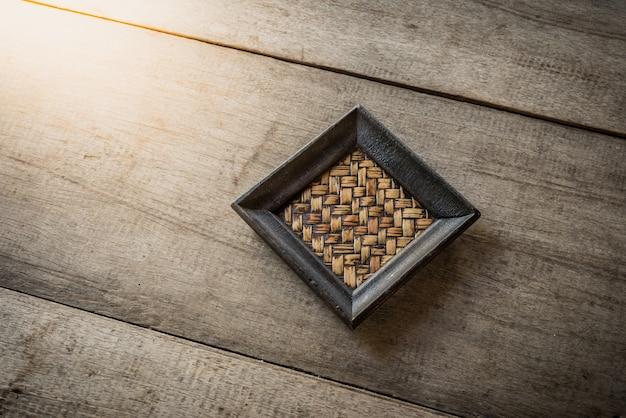 Old bamboo coaster on wooden Premium Photo