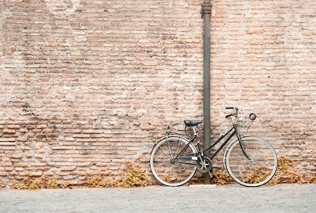 Old black bicycle against a bricks wall Premium Photo