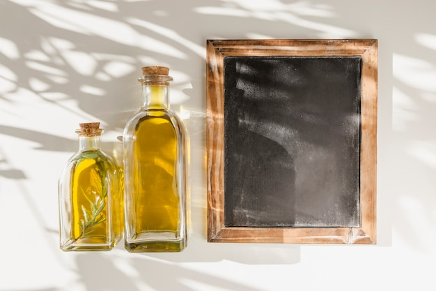 An old blank wooden frame slate with two oil bottles against the wall Free Photo