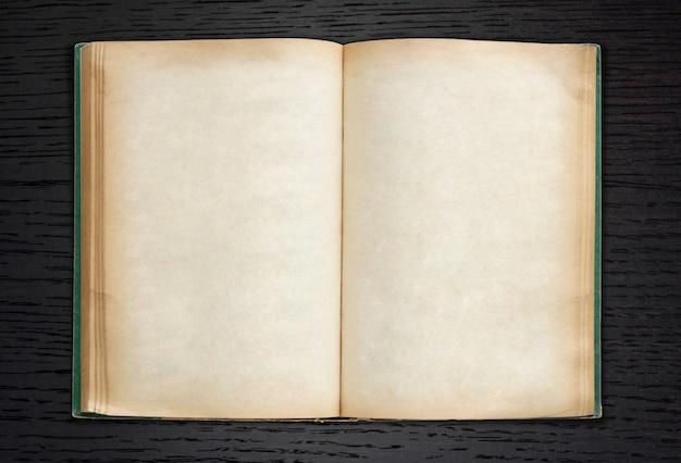 Vecchio libro aperto su sfondo scuro legno Foto Gratuite