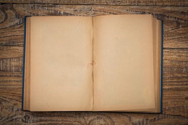 Vecchio libro aperto su un tavolo di legno visto dall'alto Foto Gratuite